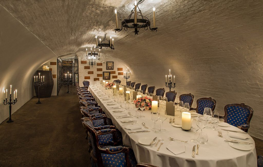 an exposed bricked event Space with an arched ceiling has been set up for a private meal. the long table has been set and there are blue chairs pressed up against the table. There are large candles handing from the ceiling.
