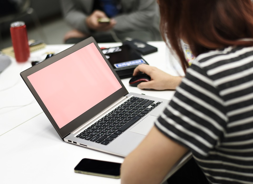 a woman wearing a black and white stripy top is sitting at her desk on her laptop logging contact details after a networking event