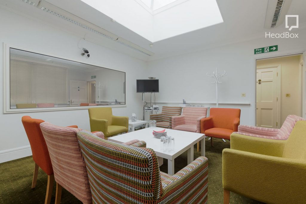 light coming from a large sky light shines down on a meeting room with a white coffee table that's surrounded by brightly coloured chairs. All the walls are painted white and one is home to a large two-way mirror. there is small HD screen in the corner of the room.