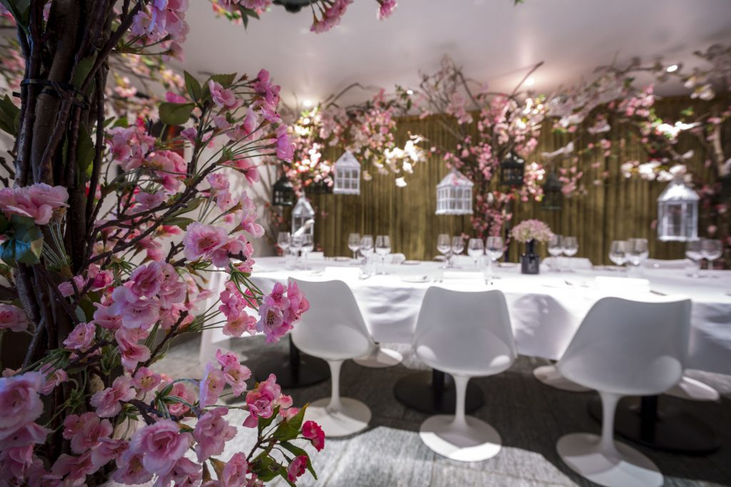 an elegant white private dining is situated in a room thats covered with pink flowers - there are white bird caged hanging amongst the flowers and white chairs are pressed up against the table