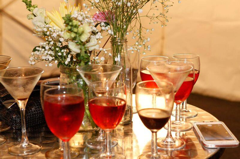 Assorted glasses filled with various beverages on a table with a phone, purse and two vases of wild flowers.