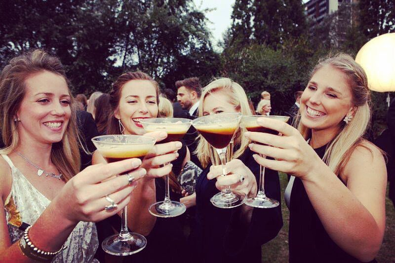 Four women toast espresso martinis towards to camera.