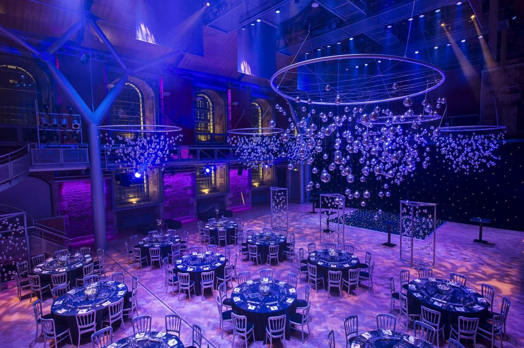 a large church venue which is set up for a giant party - there are several round tables with chairs around them set up for a banquet. Hanging from the ceiling are large chandeliers with glass balls.
