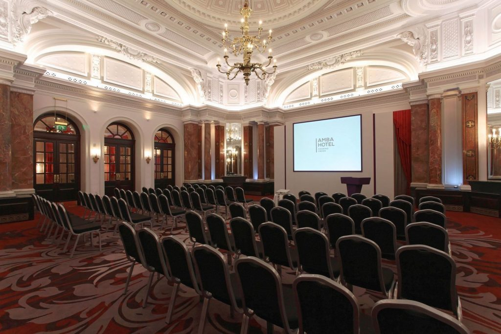 a regal interior of a conference venue shows a large chandelier hanging from the white ornate ceiling. The red pattern carpet has chairs placed on it that are facing a large screen which reads 'Amba Hotel'