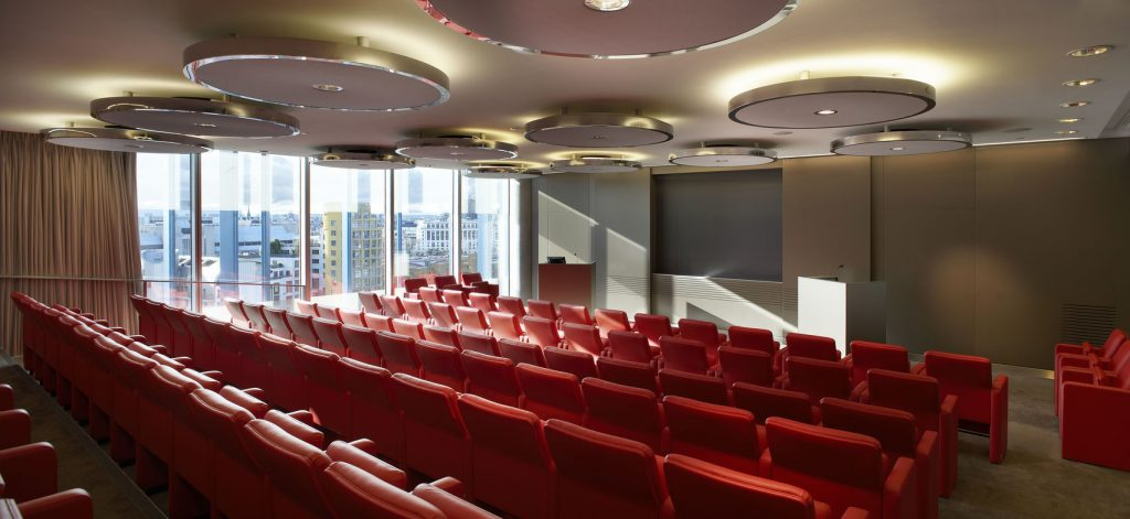 a conference room is flooded with natural light with floor to ceiling windows on the back wall. The red rows of chairs are all facing a large screen handing on the back wall.