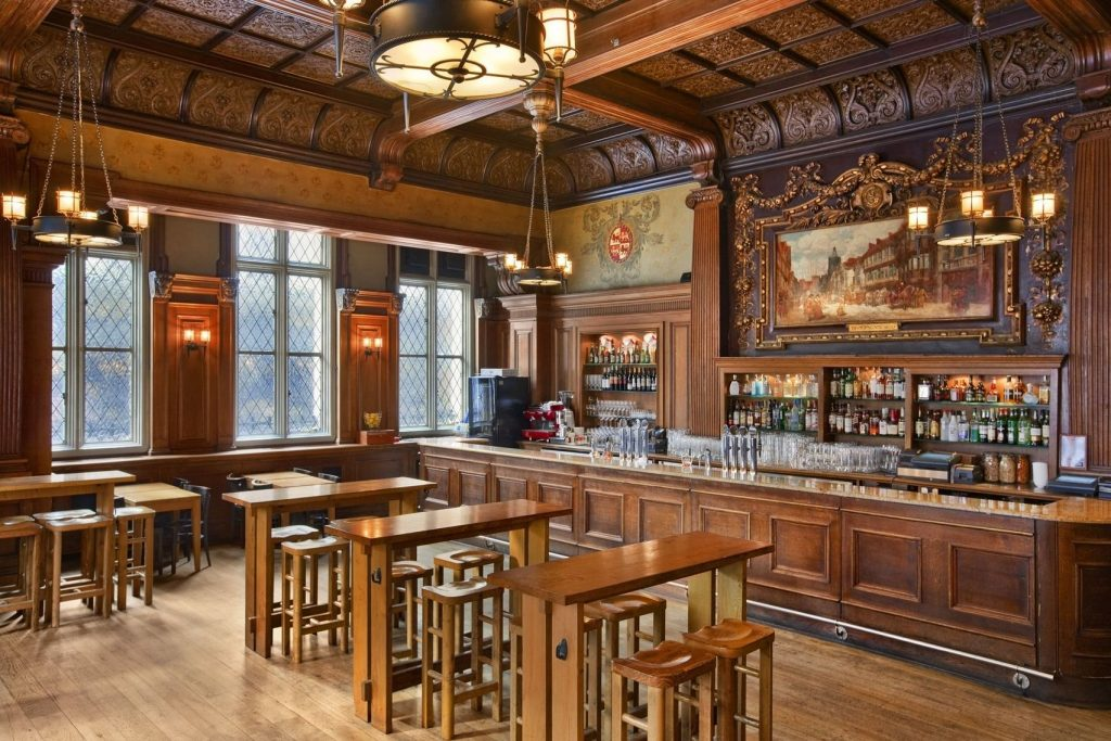 a traditional pub venue with a wooden bar, tables and chairs. the back wall has a grand painting hanging on it with golden decor around it.