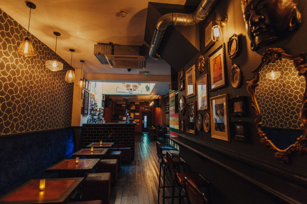 a quirky underground bar with mirrors and photos hanging all along it.
