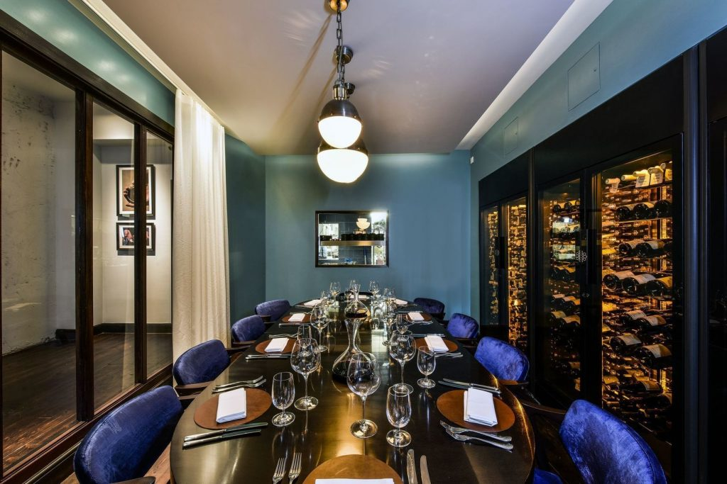 a wall is stocked from floor to ceiling with bottles of wine in a built in fridge. The walls of this private dining room are blue and the deep brown tables has purple chairs around it.