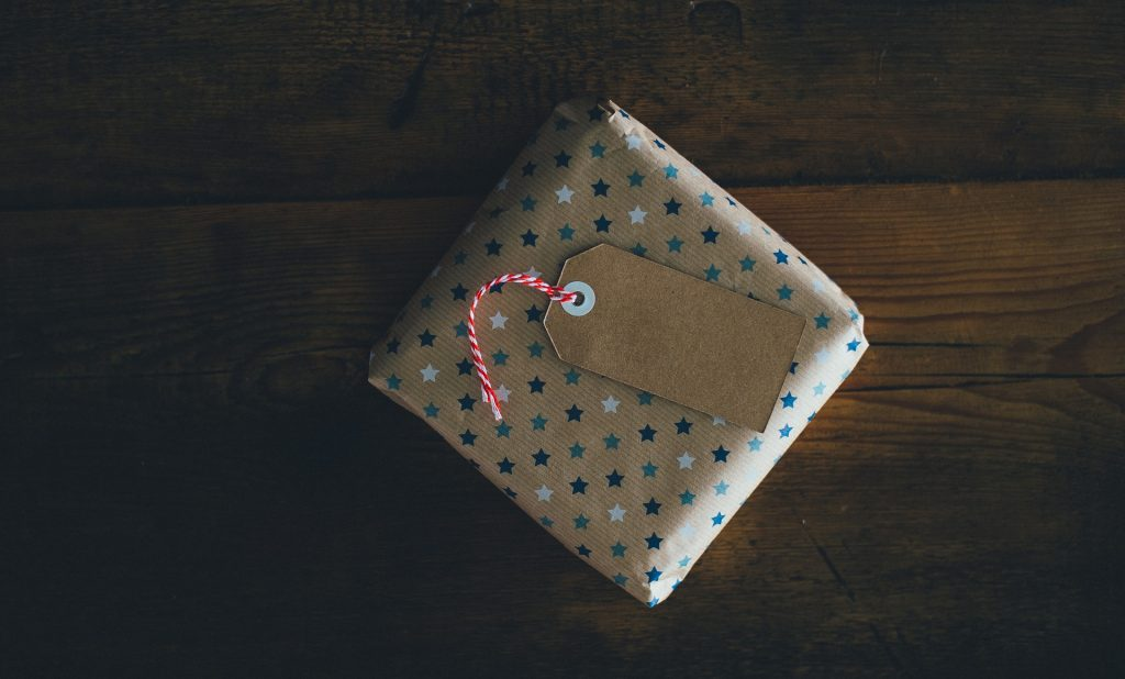 a square gift wrapped in brown paper with blue stars on with a blank name tag rests on tip of a dark wooden table top.