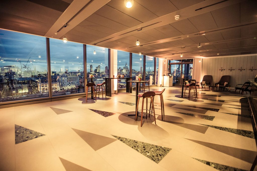 a large venue with a floor to ceiling window overlooking London. The floor is white with grey and patterned triangle on it and there are a few cocktail tables posted around the room.