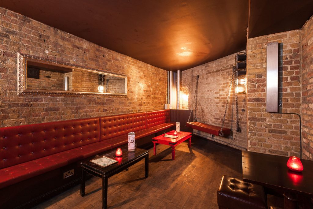 an brick walled venue with a red leather banquet seating around the edge - there are wooden coffee tables in the centre of the room and a long mirror on the wall