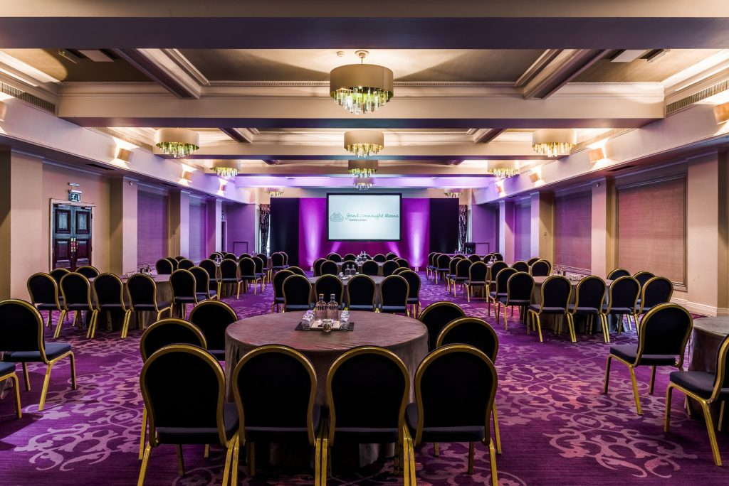 purple lit room with round tables