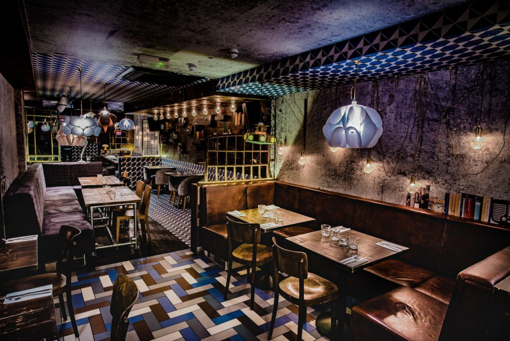 a dark restaurants with a quirky tiled floor has beautiful jelly fish lightshades hanging from it. There are brown tables and chairs set up in random formations across the floor