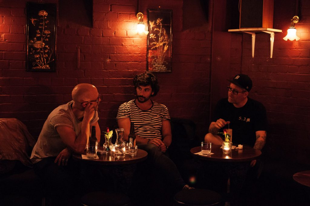 a dark bar setting with three men sitting around small tables in the middle of a conversations. the red brick walls have low-lit lights hanging on them