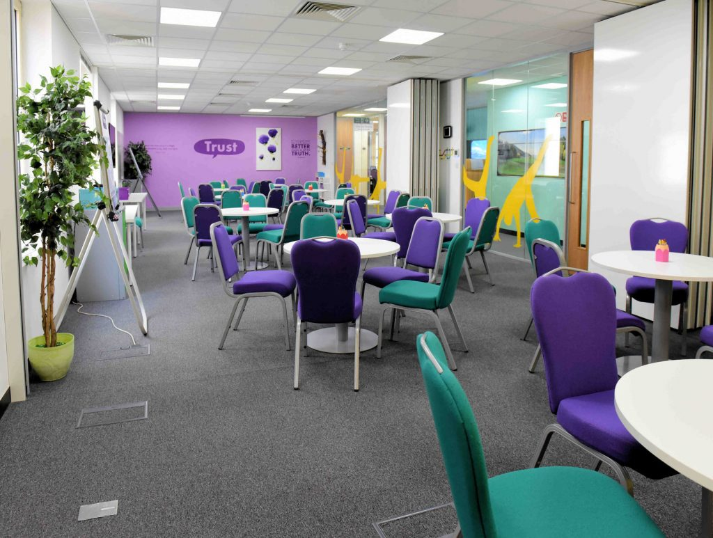 a large conference centre is set up with circular metal tables and teal and purple chairs placed around them. The back wall is also bright purple with a speech bubble that reads 'trust'