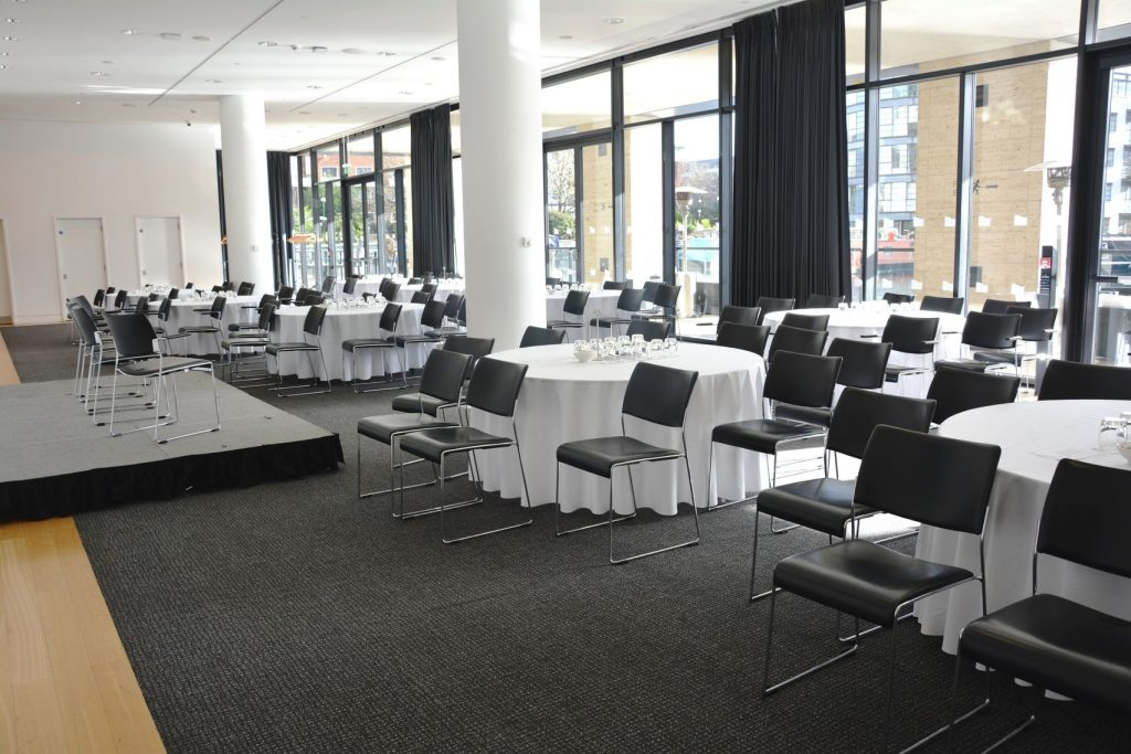 a large white conference room with black carpet is set up with white tables and black chairs all facing a small raised stage. there is a floor to ceiling window that covers the back wall