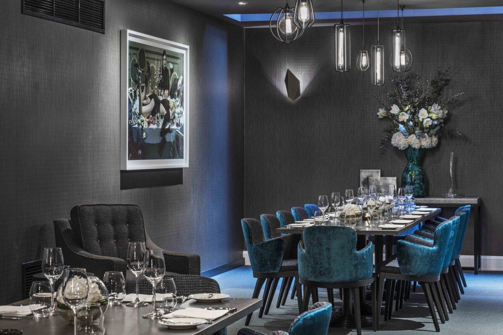 a grey private dining room with a abstract painting on the wall has a long brown table in the centre of the room. This private dining tables blue chairs pushed up against it and there is a beautiful bouquet of flowers on a smaller tables at the back of the room.