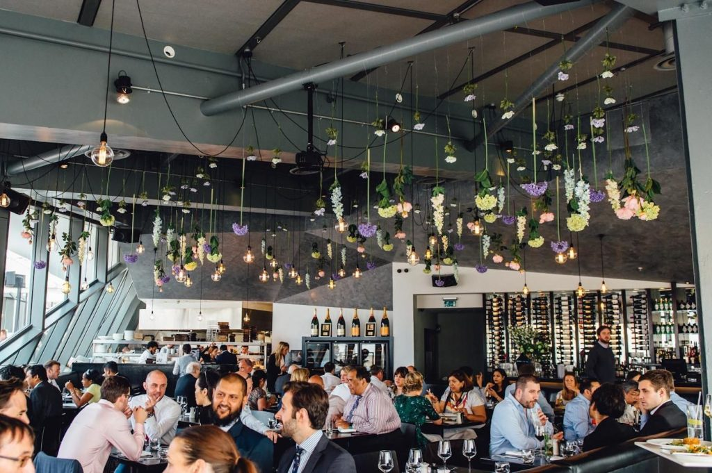a crowded restaurant is filled with people sitting under a canapés of hanging flowers