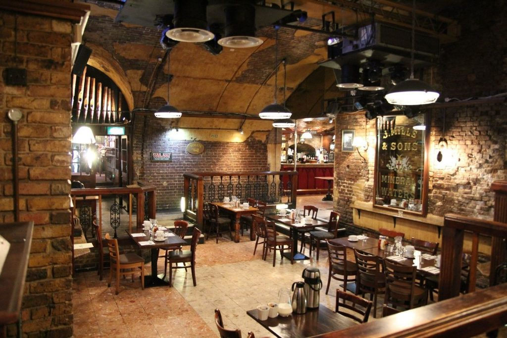 a large brick work pub with various tables and chairs around it
