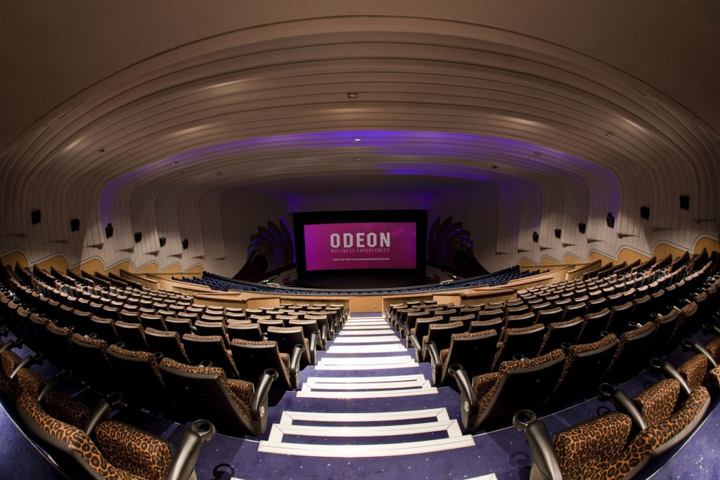 the odeon cinema in Leicester Square shows a cinema room with leopard print chairs all faces a pink screen that reads 'odeon'