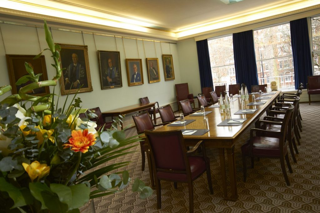 a small conference room with an oak table and brown leather chairs placed around it - the plain walls are decorated with portraits of important men and there is a brightly coloured flower in the foreground of the shot