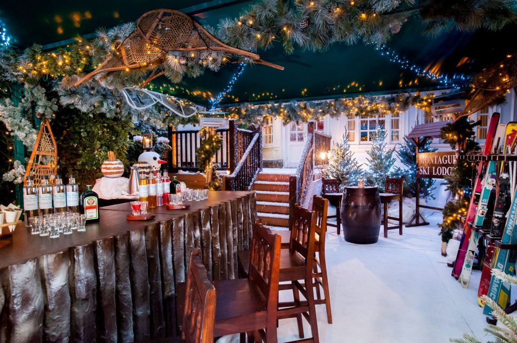 a traditional ski lodge with snow on the ground and snowmen at every corner. There is ivy and mistletoe hanging from the ceiling with fairy lights in amongst it to create a festive feel to the venue. There are skis proped up in the corner and shot glasses with a bottle next to it on the wooden bar.