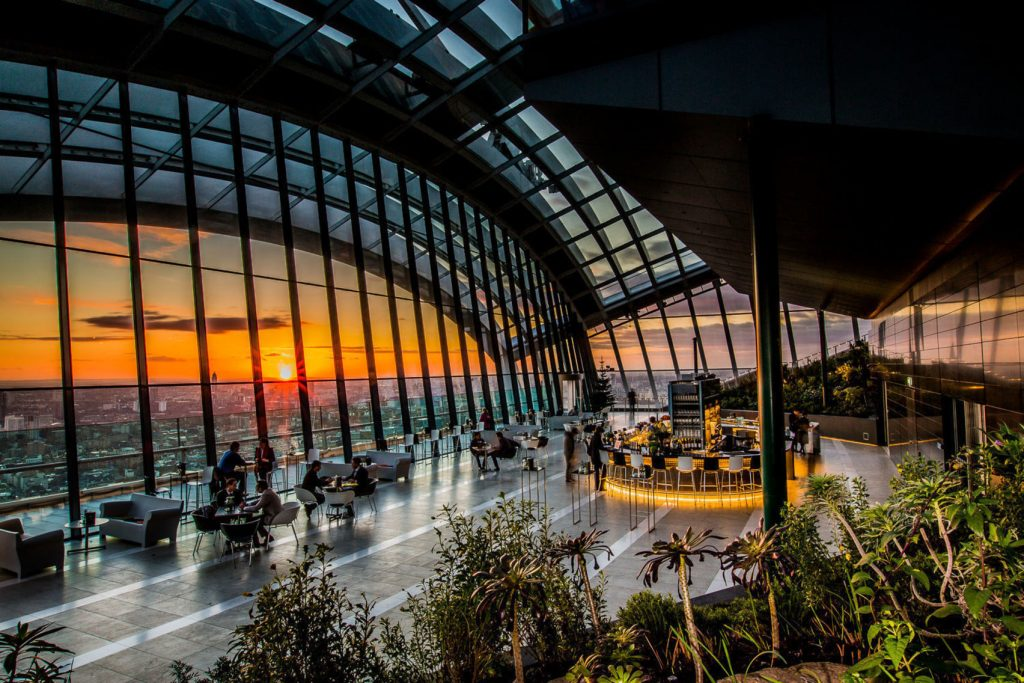a large event space with a huge floor to ceiling window that overlooks the sun setting across the London skyline.