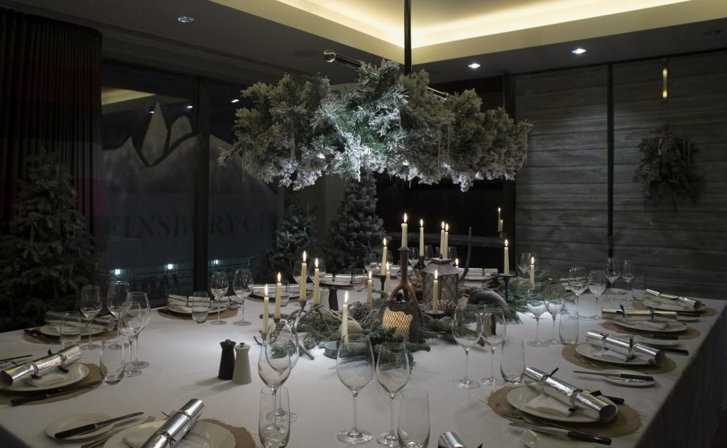 a beautifully set private dining table which has a canapé of ivy hanging from the ceiling. in the centre of the table there is a centre piece in the middle of the table with ivy and candles.