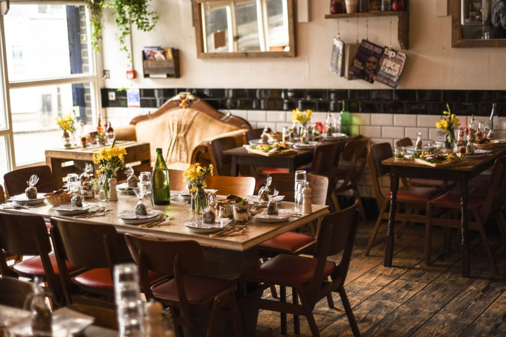 a small and quirky tap room with wooden tables dotted around the room that are set up for a dining event. There are vases on the table with yellow daffodils.