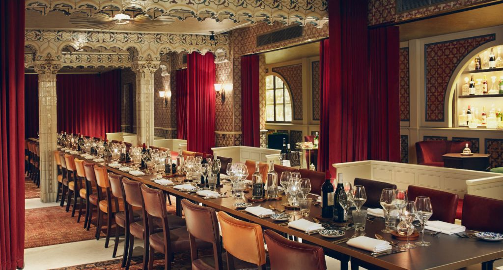 the victorian bath house is a regal looking room with red curtains hanging along the walls. There is a long oak table running down the centre of the room which is set up of a private dining event.
