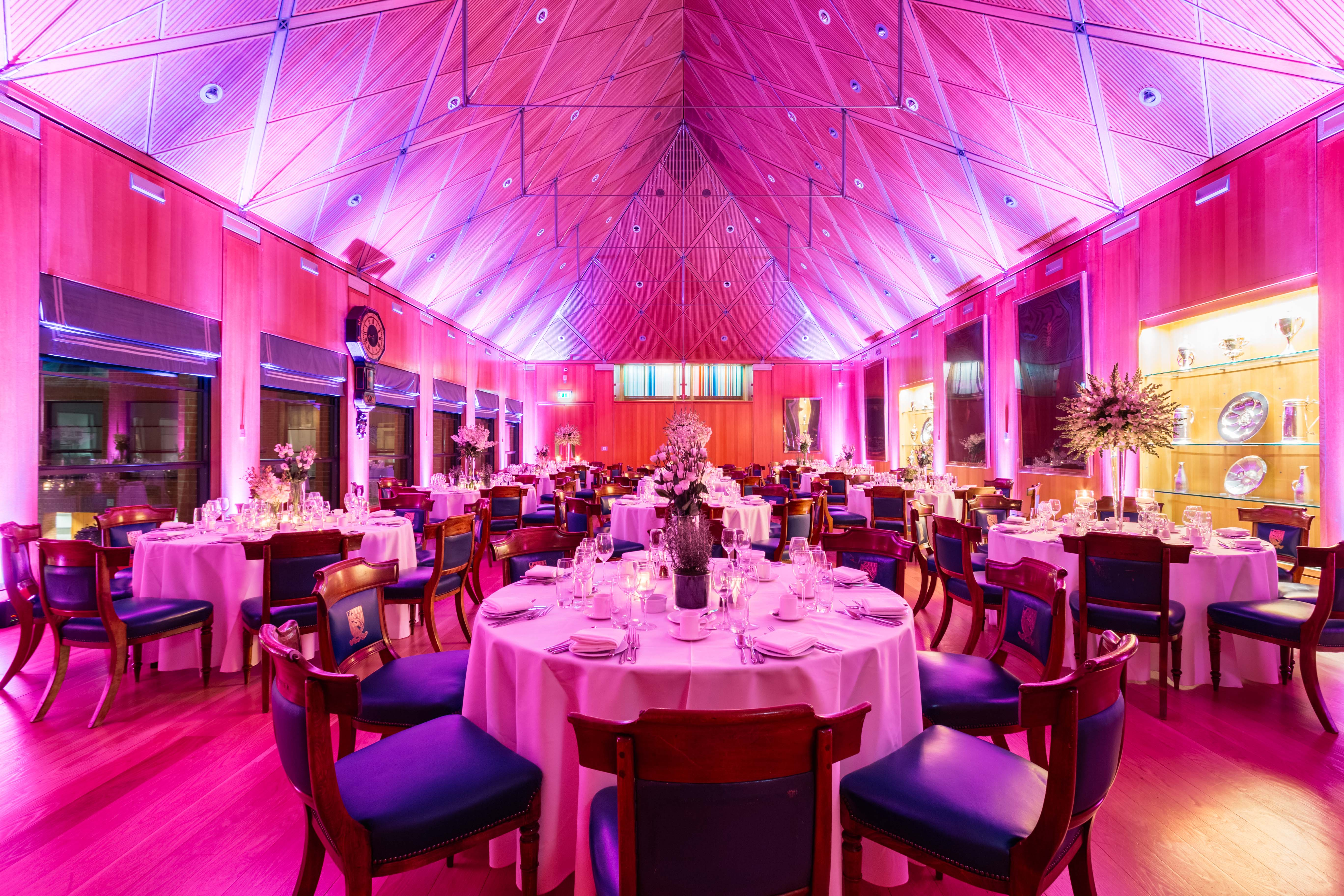 A large hall in Haberdashers' Hall with pink light and round cabaret tables