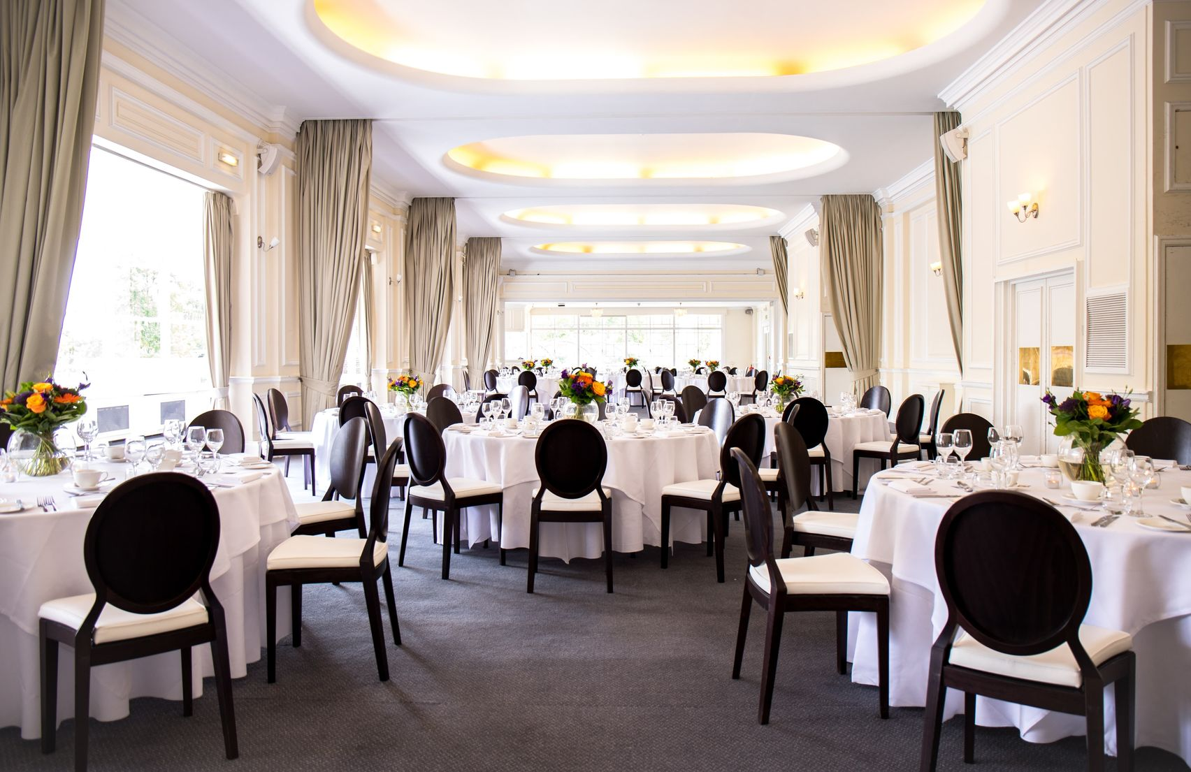A large naturally lit room decorated with white tablecloths and surrounded by black dining chairs