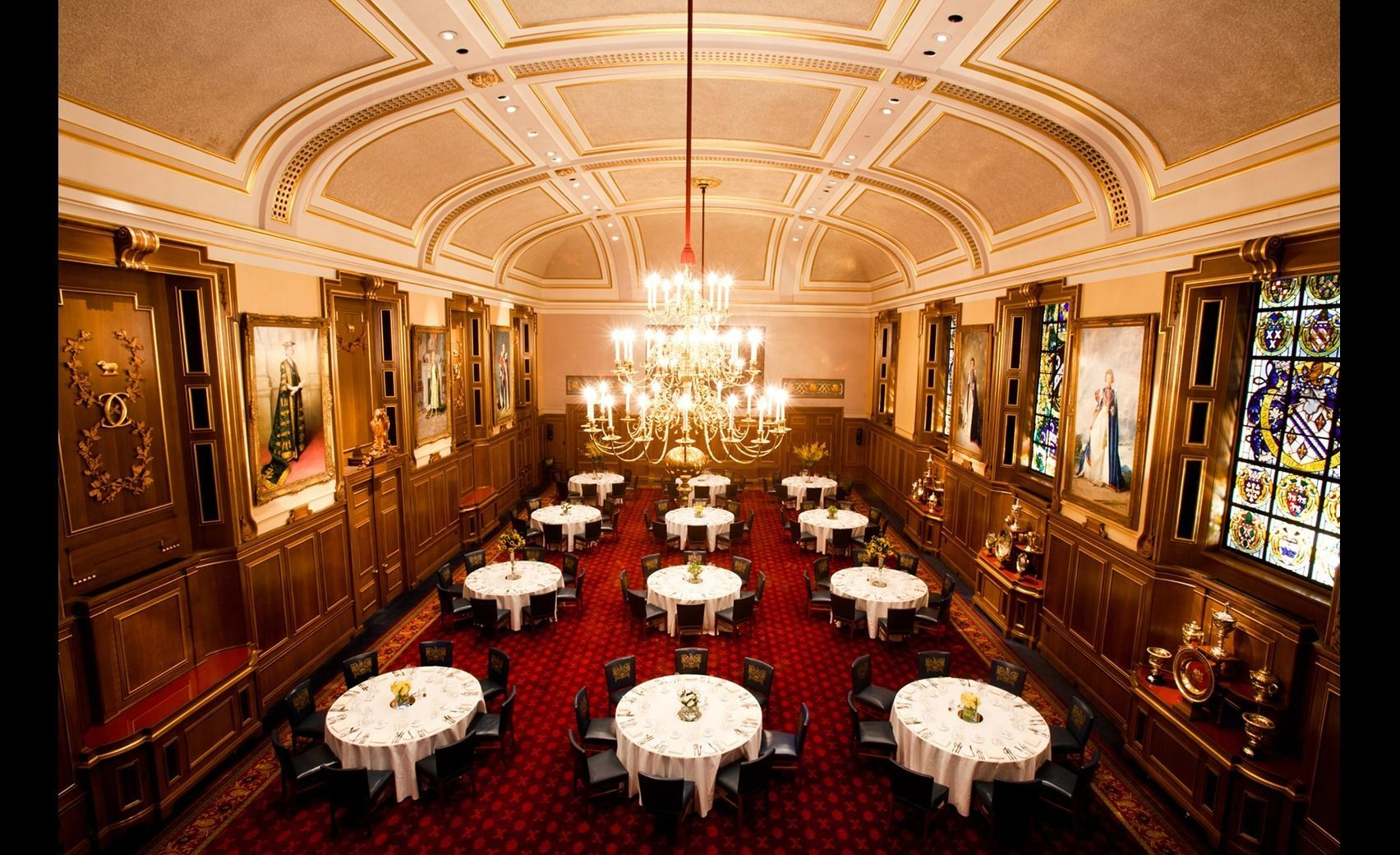 A large livery hall that has circular tables and red carpet