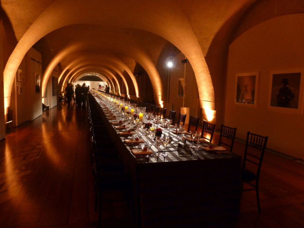 a circular roofed venue with a long private dining. the room is dimly light with candles on the table creating shadows on the wall