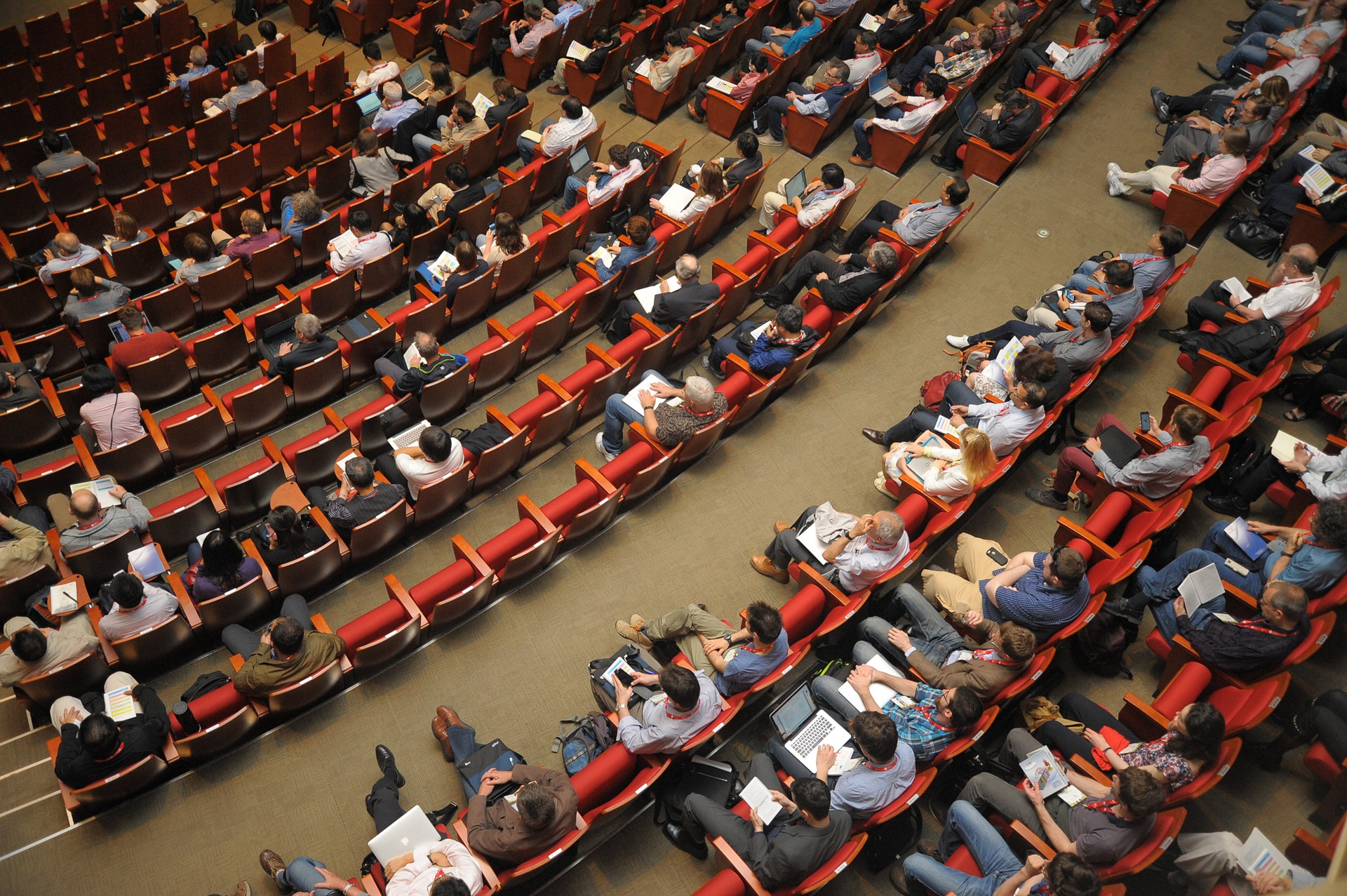 An overhead image of people sat in red chairs