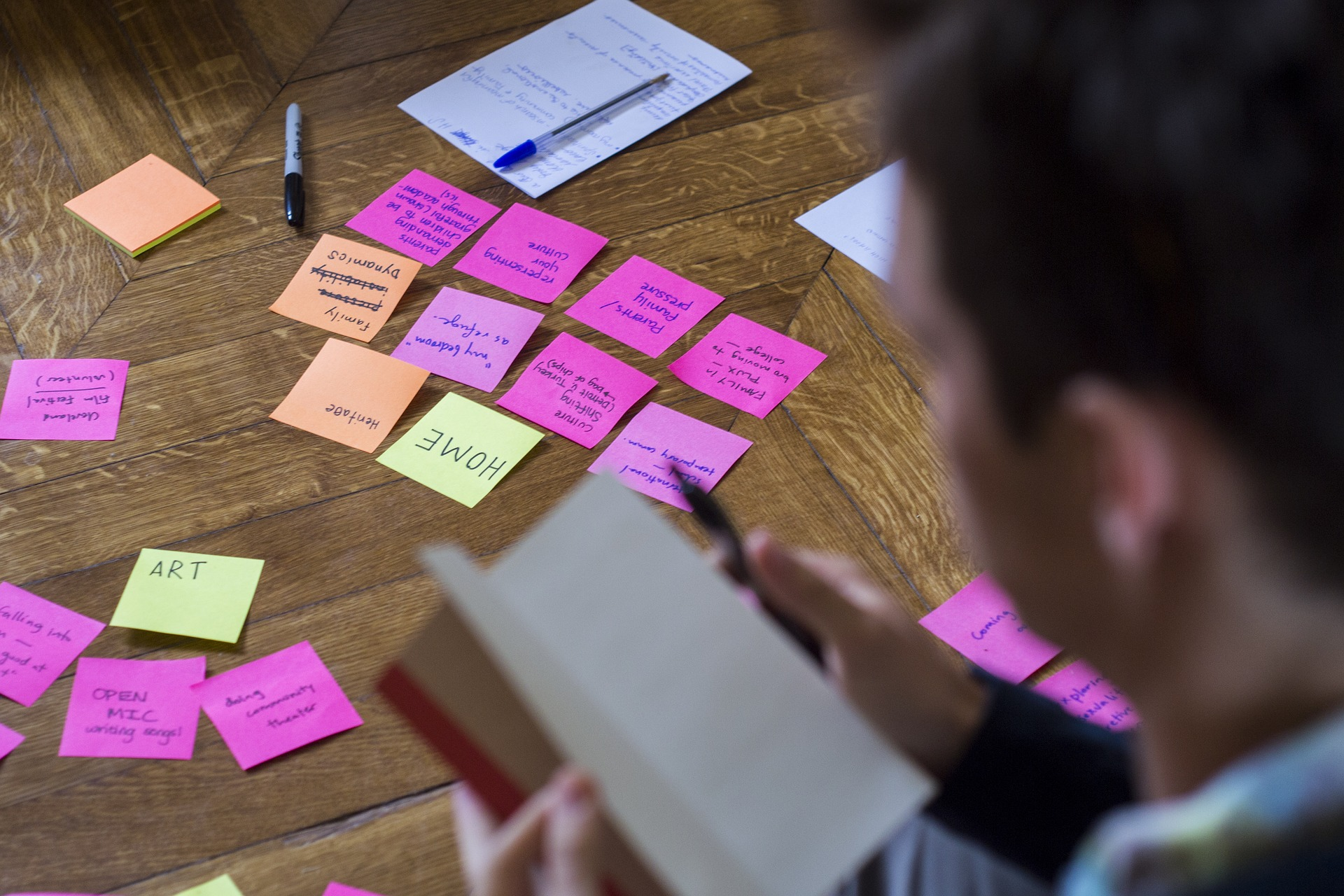 A man reading a book in front a table of post-it notes