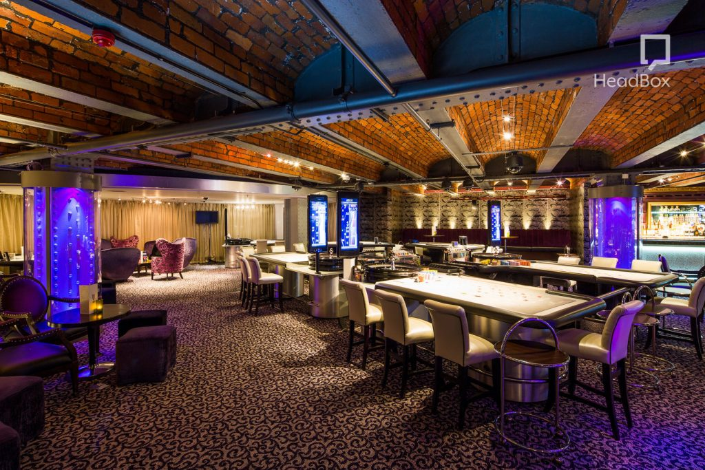 casino tables fill a large event Space which has an exposed brickwork ceiling.