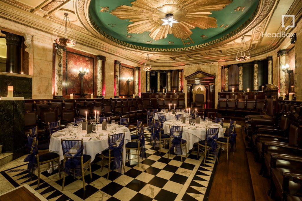 the Masonic temple is an impressive ballroom with tiled flooring and a beautiful chandlier ceiling.