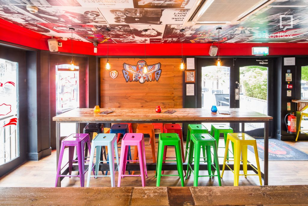 a bright bar table with multi colour cocktail chairs pressed up against it. This quirky Space has a ceiling which has been plastered with old fashioned music posters and alum covers.