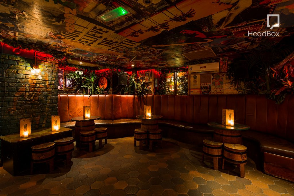 a dimly light bar with exposed brickwork walls and low wooden tables and chairs. There are posters and graffiti on the ceilings and candles on top of each table.