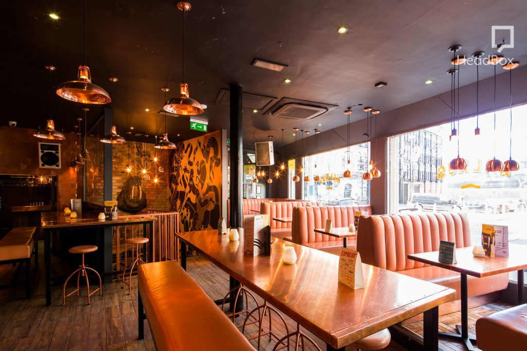 this bar is floor with natural light from the floor to ceiling window on the back wall. There are quirky, modern light fixtures hanging from the ceiling as well as booth seating along the back wall of the venue