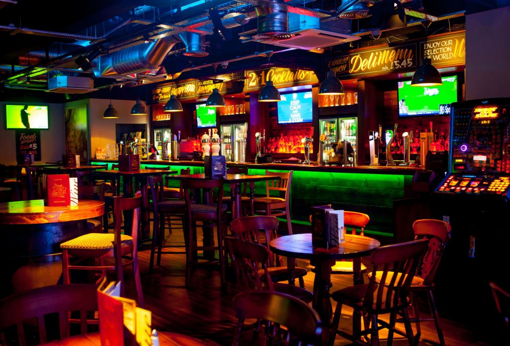 a dimly lit bar which lots of neon and bright artificial lights covering the back wall.