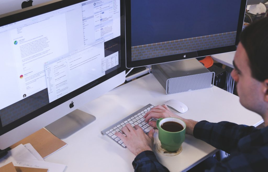 a man is sitting at a desk with two computer screens. One of the screens has several tabs open and the other is a blue screen. On the desk is a hot cup of coffee.
