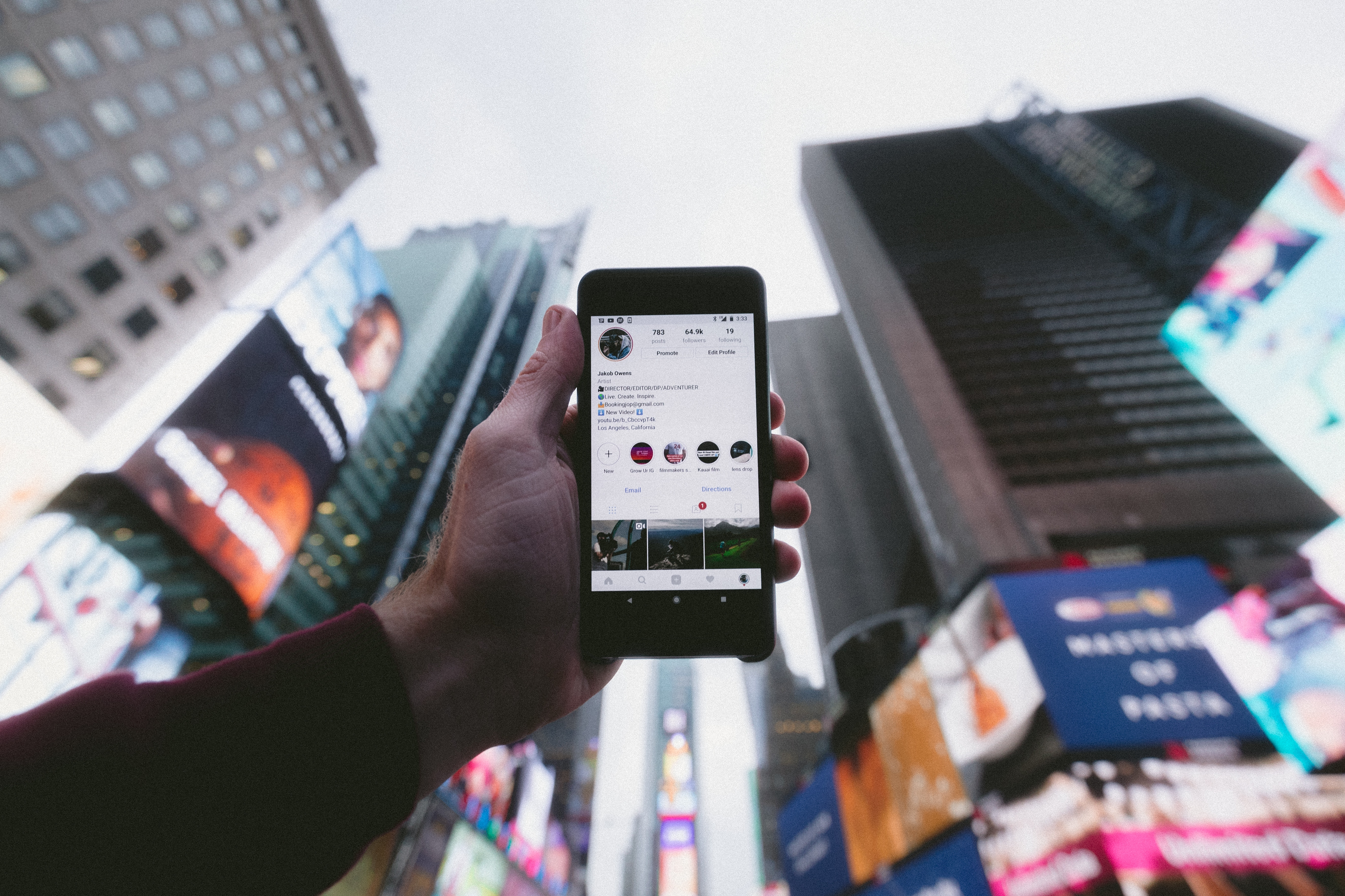 Person holding phone in front of buildings