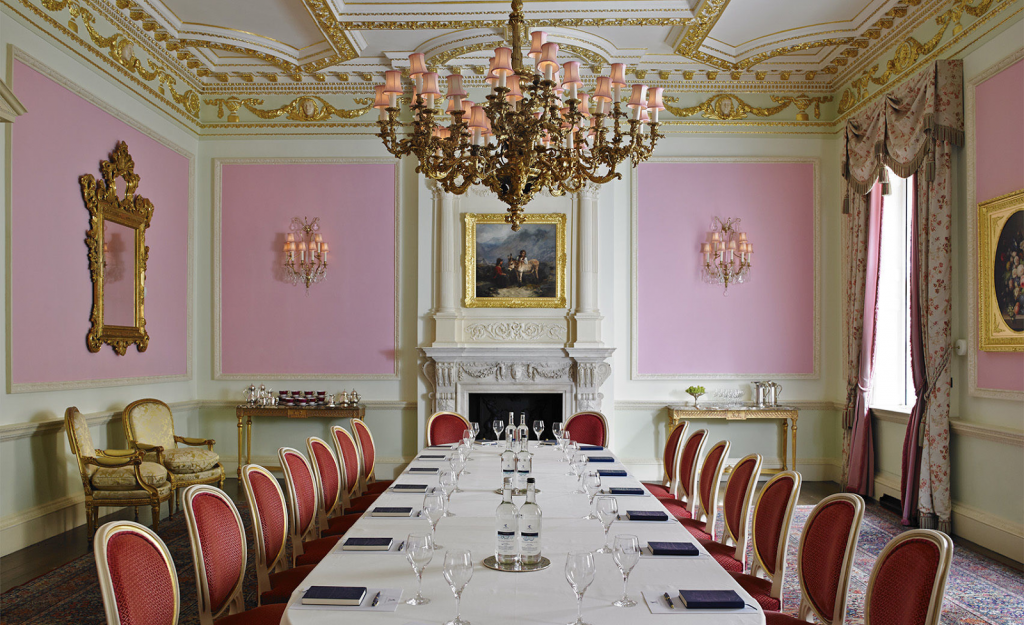 a grand dining room with a chandelier hanging from the ceiling. The walls are pink and white with golden ornaments and a long white dining table in the middle of the room. The table has red chairs pushed up agianst it.
