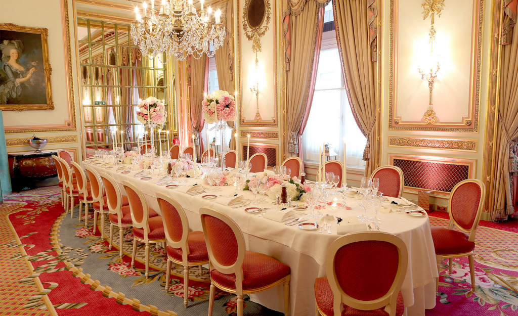a fancy private dining room with a long table in the middle of the room with a white table cloth and red chairs pushed up around it. there is also a glass chandelier hanging from the ceiling and a painting hanging on the wall of a lady holding a glass in her hand.