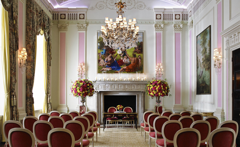 a chandelier is hanging from the ceiling of a grand room with walls that are pink and white with golden ornaments. The table has red chairs pushed up against it. On the back wall there is a large fireplace with a grand painting hanging above it.