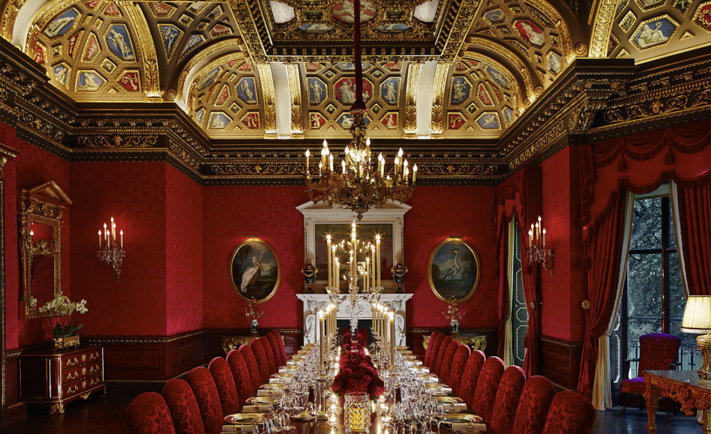 a grand dining room with deep red walls and a golden aztec ceiling with a chandelier hanging down from it. There is a long dining table in the middle of the room with red material chairs pushed up against it.