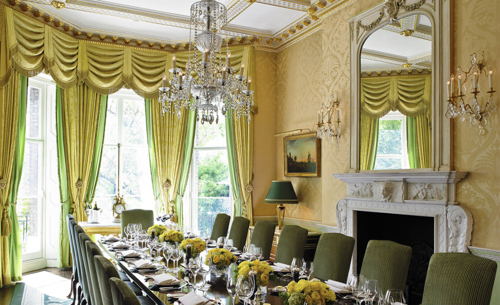 a light and bright dining room with cream walls and green curtains. There is a large mirror on the left wall.