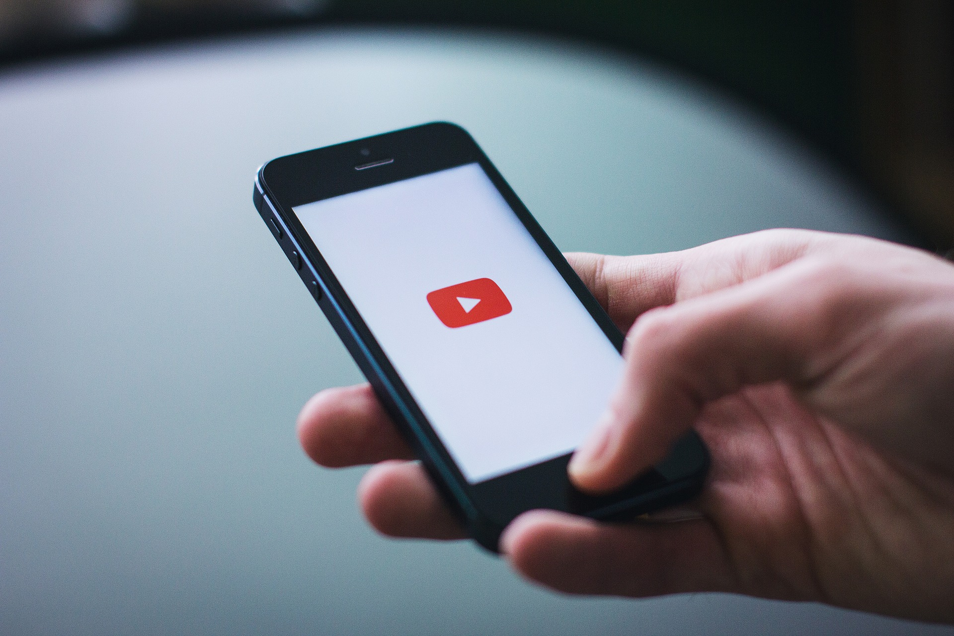 An image of a hand holding a phone with the YouTube logo on it